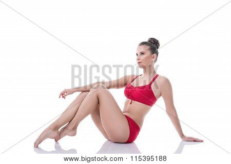 Pretty gymnast sitting, pulling her knees to chest