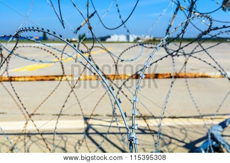 Close-up Of A Barbed Wire Fence. Horizontal View Of A Barbed Wire Fence Surrounding An Airport.