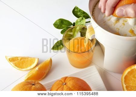 Hand Squeezing An Orange On A Kitchen Table Elevated View