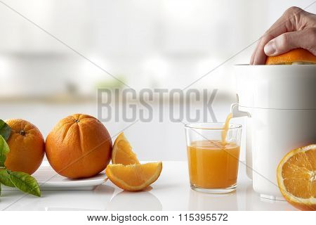 Hand Squeezing An Orange On A Kitchen Table Horizontal Composition