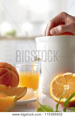 Hand Squeezing An Orange On A Kitchen Table Vertical Composition
