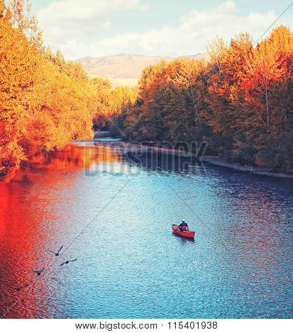 a river flowing in autumn with a kayaker paddling in the water toned with a retro vintage instagram filter effect app or action