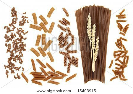 Whole wheat pasta varieties of gomitini, tortiglioni, fusilli,  penne, spaghetti with wheat ears and mini fusilli over white background.