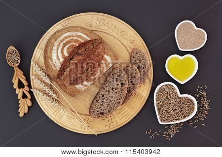 Rustic homemade rye bread on wooden board with wheat sheaths, yeast, olive oil and rye grain in heart shaped dishes and spoon.
