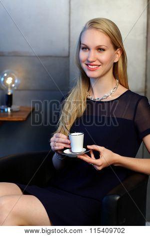 Happy elegant nordic type businesswoman having coffee-break, smiling, looking away.