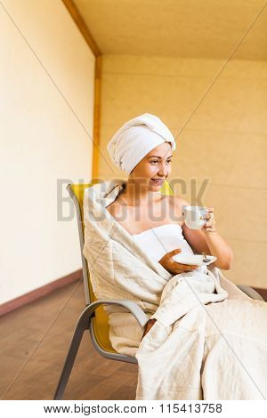 Young woman with white cup of coffee or tea after bath in towel