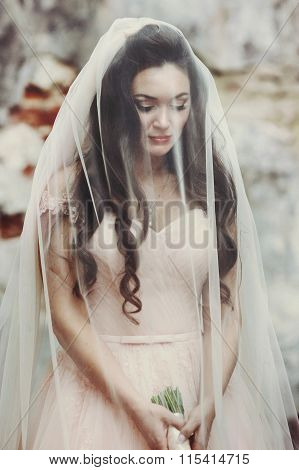 Sensual Beautiful Brunette Bride Holding A Bouquet And Hiding Under Her Veil Outdoors