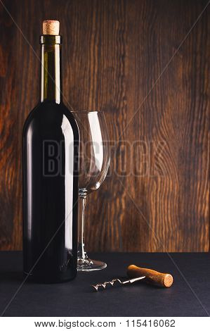 Full Bottle Of Wine, Empty Glass And Corkscrew