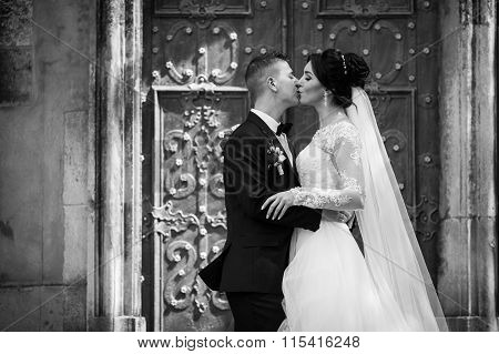 Happy Couple Of Newlyweds Kissing In Front Of Old Church Door B&w