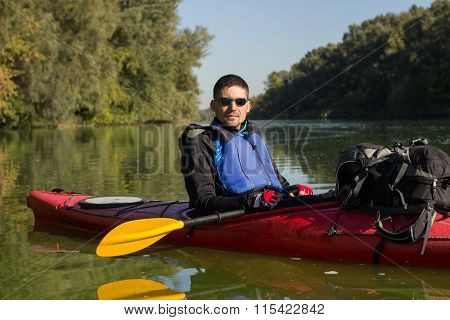 The man is kayaking on the river.