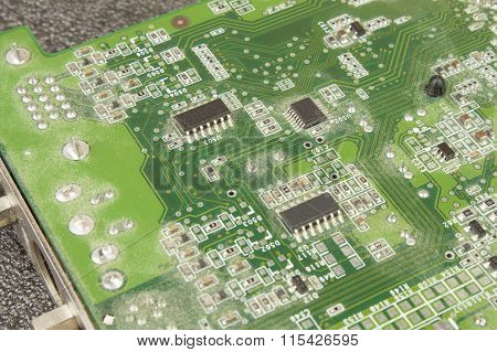 A dusty green computer component. Detail of a dusty computer mainboard