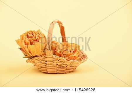 Small Basket Of Dried Roses On Beige Paper
