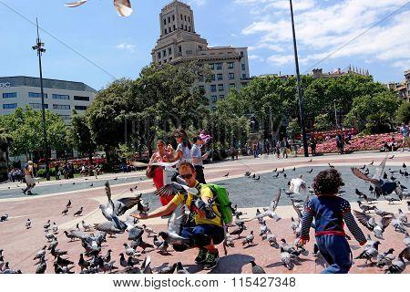 Barcelona, Spain - May 17, 2014: Placa Catalunya. Tourists Feeding Pigeons.