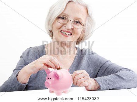 Senior Woman Saving Money In A Piggy Bank