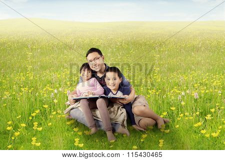 Father And Children Read Book On Meadow