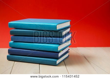 Stack of old hardback books, diary, on wooden deck table and red background.
