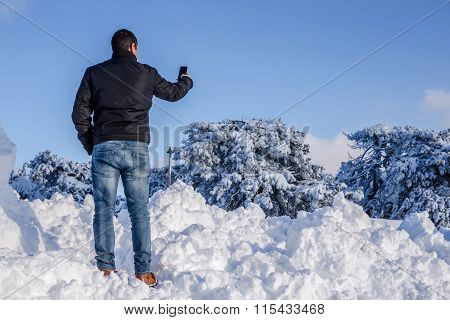 Man Taking Selfie With Smartphone On The Snow