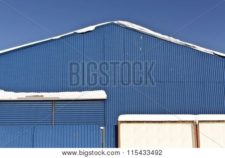 Snow On The Roof Of Blue Metal Warehouse.