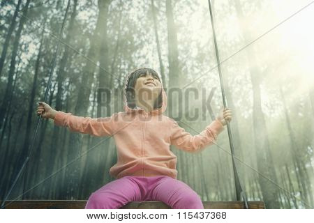 Little Girl Sitting On A Swing Outdoors