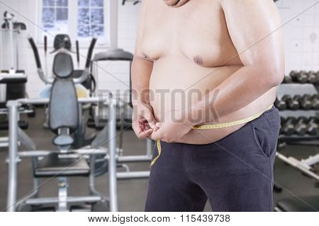 Overweight Man Measuring His Belly At Gym