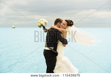 Nice newlyweds are holding each other on the sea background.