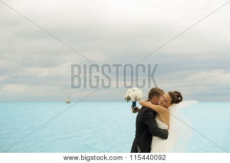 The groom is holding her bride on the sea background.