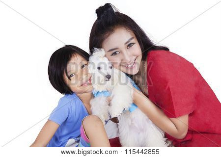 Woman And Her Daughter Hugging Maltese Dog