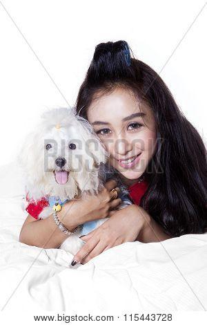 Woman Hugging Maltese Dog On Bed