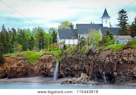 Waterfalls behind a church.  Edge of Canada at Margaretsville,  Bay of Fundy.  Low tide in Nova Scot