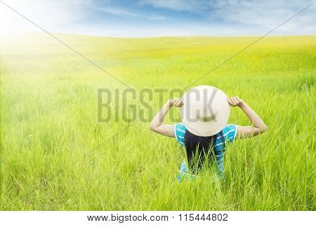 Woman With Hat Sitting On The Green Meadow