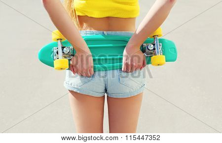 Beautiful Girl With Skateboard In Shorts, View From Back