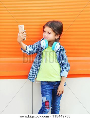 Happy Smiling Child Taking Picture Self Portrait On Smartphone In City Over Colorful Background