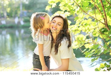 Daughter Child Kissing Happy Mother In Summer Day
