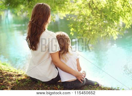 Happy Mother And Child Daughter Sitting Together In Summer Day