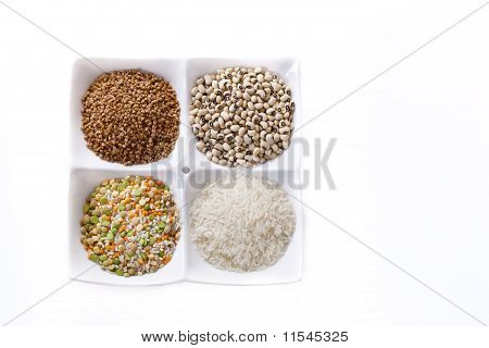 Four kinds of groats lie on a plate on a white background