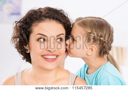 Daughter is kissing her smiling mother.