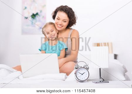 Mom and daughter in the bedroom with laptop.