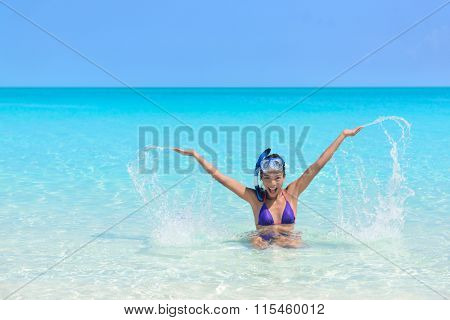 Beach holiday woman playing in the ocean. Asian young adult wearing a snorkel scuba mask having fun splashing water with arms up and swimming in vacation resort travel destination.