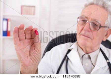 Doctor Showing Red Tablet