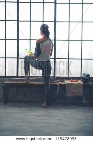 Rear View Of Woman Looking Out Window Holding Water In Loft Gym