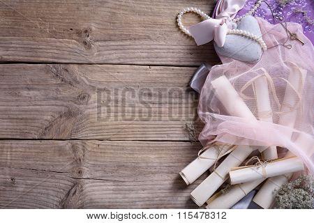 Wedding accessories: ceramic heart, vintage invitation scrolls, pink veil,pearl on wooden background