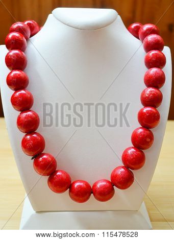 Traditional Ukrainian round red bead made from wood on white mannequin