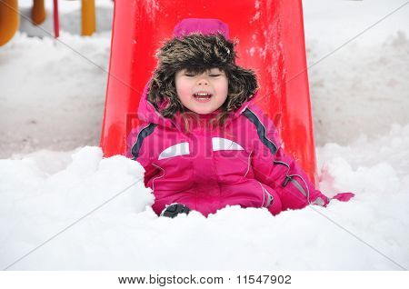 Cute toddler girl sitting on snow at the children's playground
