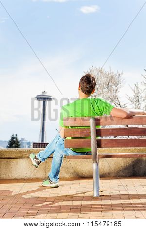 Man with space needle on background in park