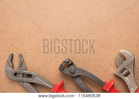 Set Of Pump Plier, Plier And Wrenches. Tools Over A Wood Panel. Top View With Copy Space.