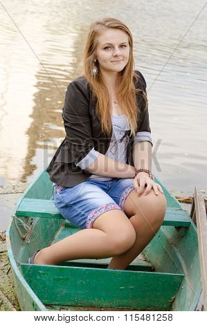 Beautiful young female wearing sailor striped dress sitting in boat