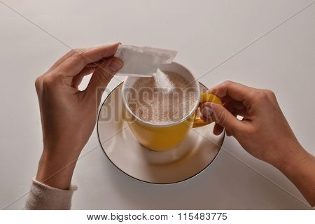 Pouring sugar on coffee cup.