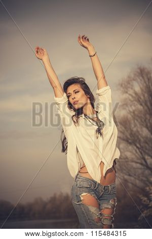young woman in white shirt and jeans with arms up stand in wind, natural light, outdoor summer day