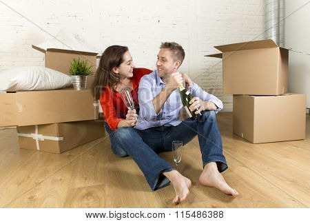 Happy Couple Sitting On Floor Unpacking Together Celebrating With Champagne Toast Moving In New Hous