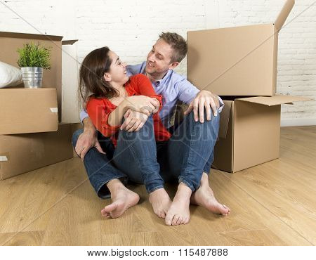 Happy Couple Sitting On Floor Celebrating Moving In New Flat House Or Apartment